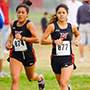 Photo of two female CSUN track athletes running.