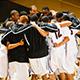 Men's basketball team in huddle.