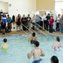 Photo of people in water at Brown Center with spectators watching.