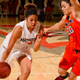 Female Matador basketball player dribbling ball past a defender