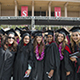 CSUN graduates standing together on commencement day with Oviatt Library in the background.