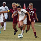 CSUN soccer player dribbling the ball against two LMU defenders.