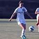 Women's soccer player dribbles the ball.