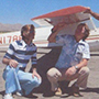 Brian Dinelli as a student kneeling next to an airplane.