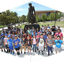 Young people from Dodgers RBI stand for a group photo in front of the CSUN Matador Statue.