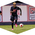 A men's soccer dribbles the ball.