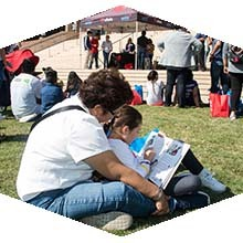 A mother and daughter sit on the lawn in front of the Oviatt Library to read a book at last year's Feria de Education.
