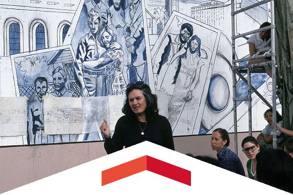 CSUN alumna Judith Baca stands before her Great Wall mural.