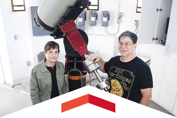 Professors Cristina Cadavid and Damian Christian pose with a large telescope.