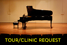 Tour-Clinic link. Piano on a darkened stage.