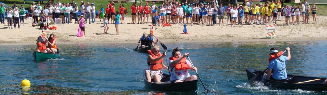 teams of two rowing boats with onlookers cheering