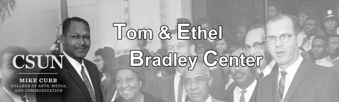Tome Bradley standing in a group of people.  Tom & Ethel Bradley Center banner.